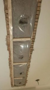 Cellulose blown between floors in a residence through a slot cut in the ceiling.